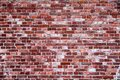 Old and weathered simple grungy red brick wall marked by the long exposure to the elements as texture background Royalty Free Stock Photo