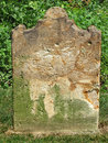Old weathered tombstone and worn nameless stone slab grave Royalty Free Stock Photo