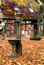 Old well pump an in a garden in autumn Stock Image