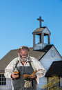 Old west drunkard holds bible a in front of church Stock Photo