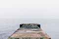 Old wet concrete pier on a cloudy day Royalty Free Stock Photo