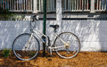Old White Bicycle Chained to Green Pole Stock Image