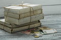 Old white books with money and coins on wooden background