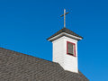 Old white rural church steeple and belfry against blue sky Stock Images