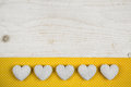 Old white shabby chic background with five hearts and yellow fab ancient fabric on the frame Royalty Free Stock Images