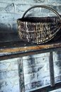 Old wicker basket standing on a shelf next to a wooden ladder
