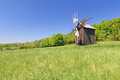 Old wind mill on a spring meadow with blue sky Stock Images