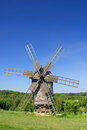 Old wind mill on a spring meadow with blue sky Stock Photos