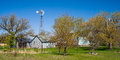 Old windmill, blue farm buildings, spring, minnesota Royalty Free Stock Photo