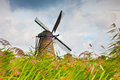 Old windmill canal against cloudy sky kinderdijk holland Stock Photos