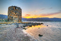 Old windmill ruin on Crete at sunset Stock Images