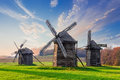 Old windmills on a background of forest and sky wooden with blurred clouds in autumn evening national museum ukrainian Royalty Free Stock Photos