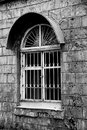 The old window behind the steel grill on the gray wall of the house Royalty Free Stock Photo