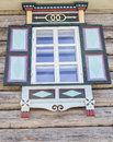Old window with with brightly painted shutters glass with a blue sky on the background of the wooden wall of the countryside log h Royalty Free Stock Photo
