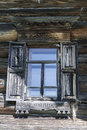Old window with glass with a blue sky on the background of the wooden wall of the countryside log house Royalty Free Stock Photo