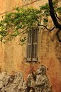 Old window of medieval house under tree on the alley city Royalty Free Stock Photo