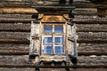 Old window with open shutters glass with a blue sky on the background of the wooden wall of the countryside log house Royalty Free Stock Photo