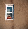 Old window with pumpkin a distressed a vintage copper shaped mold in the middle of an aged grunge stucco wall Stock Photo