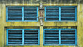 Old window shutters blue wooden in yellow wall Royalty Free Stock Image