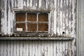 Old window of wooden house painted peeling white paint building boards chipped and from with a sill on the wall a Stock Image