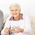 Old woman buttering a toast for senior breakfast at home Stock Images