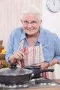 Old woman cooking in the kitchen Royalty Free Stock Photos