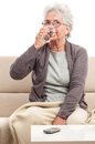 Old woman drinking glass of water with a blanket on knees senior sick isolated on white Stock Photography