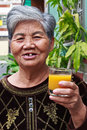 Old woman drinking juice Royalty Free Stock Photography