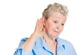 Old woman eavesdropping closeup portrait nosy surprised senior mature hand to ear trying to secretly listen in on juicy gossip Stock Images