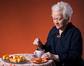 Old woman enjoying tea cup apple pie over orange background Stock Images