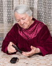 Old woman with glucometer checking blood sugar level Royalty Free Stock Photo