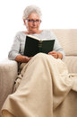Old woman at home reading book senior sitting on sofa with blanket on feet isolated on white Stock Photography