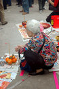 Old woman kneeling seeking blessings Royalty Free Stock Photo