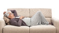Old woman laying on the sofa resting isolated white Royalty Free Stock Photography