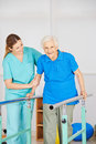 Old woman at movement exercise women on horizontal bar in physiotherapy Royalty Free Stock Images