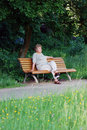 Old woman on a park bench thinking Royalty Free Stock Image