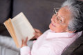 Old woman reading a book relaxing at home Stock Photos