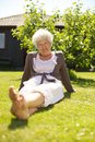 Old woman relaxing on grass sitting relaxed in backyard garden and looking at camera outdoors Royalty Free Stock Photo