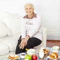 Old woman sitting at breakfast smiling set table home Stock Photo