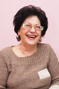Old woman smiling with glasses on an light pink background Stock Photo
