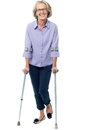 Old woman walking with crutches senior the help of Royalty Free Stock Photography