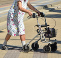 Old woman walks with a walker Royalty Free Stock Photo