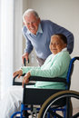 Old woman on a wheel chair , husband at the back Royalty Free Stock Photos