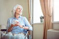 Old woman in wheelchair holding cup Royalty Free Stock Photo