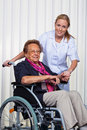 Old woman in a wheelchair and a nurse Royalty Free Stock Photo