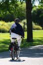 Old women on a bike is going forward through shady alley in assiniboine park winnipeg manitoba canada summer Royalty Free Stock Image