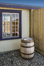 Old wood barrel beside a wooden gallery and a wooden house Royalty Free Stock Image