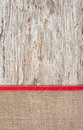 Old wood bordered by burlap and red ribbon background Royalty Free Stock Photos