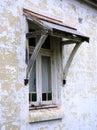 Old wood framed window flaking paint on house needing renovation Royalty Free Stock Image