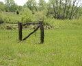 Old wood gate in a field made of tree trunks of prarie grass rural kansas Stock Image
